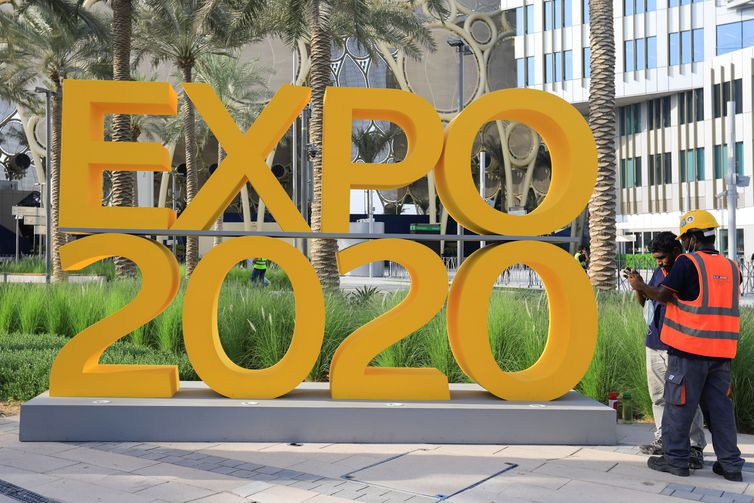 Workers are pictured next to the Expo 2020 logo ahead of the opening ceremony in Dubai